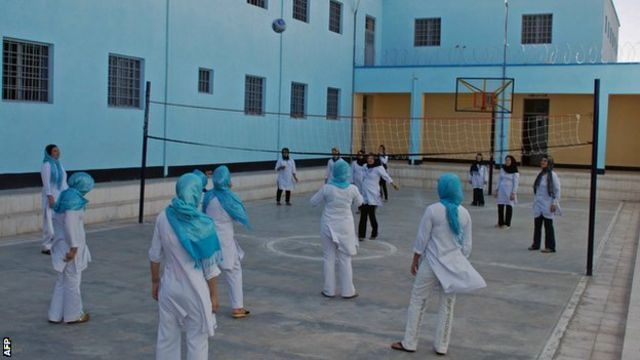 Female Afghan prisoners play volleyball at a prison in the eastern Afghan city of Herat on July 2, 2010