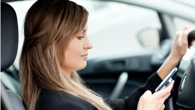 Mulher usa celular no carro