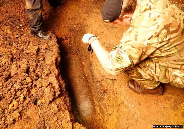 Bomb disposal experts examine the unexploded WW2 bomb