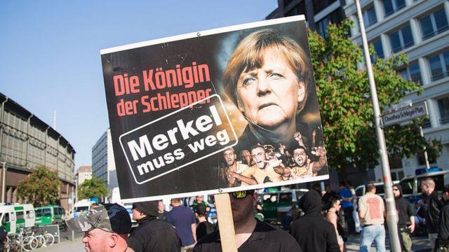 """Un manifestante sostiene un cartel que dice """"Merkel debe irse""""."""