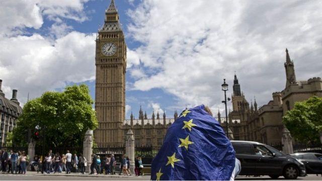 Hombre envuelto en la bandera de la UE