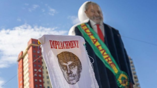 Cartaz em tecido diz Impeachment, sobre uma imagem de Jair Bolsonaro, com um boneco de Lula usando uma faixa presidencial escrita 'Lula Livre' ao fundo