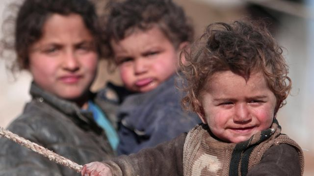 Internally displaced Syrian children who fled Raqqa city stand near their tent in Ras al-Ain province