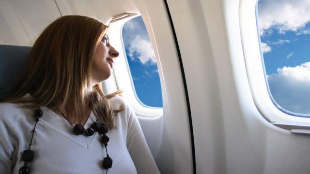 Mujer en la ventanilla de un avión.