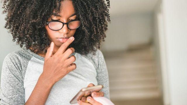 Adolescente utilisant un smartphone à la maison