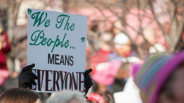Mãos segurando um cartaz dizendo 'nós, o povo, significa todo mundo'