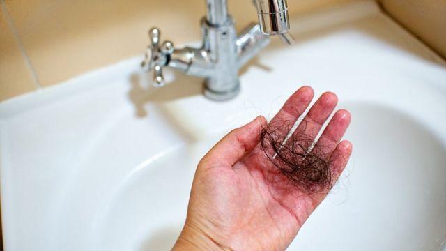 Una mano con hebras de pelo