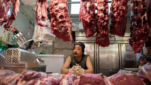 Butcher looks at meat hanging in a shop in China