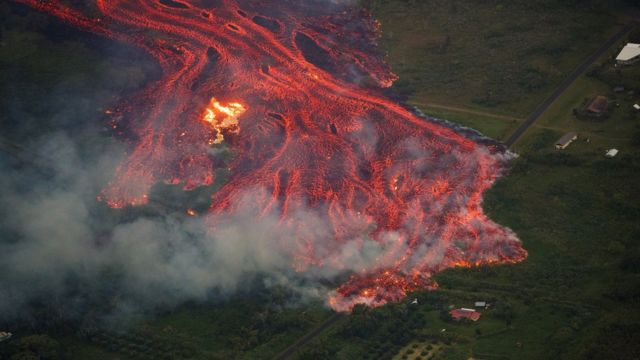 An aerial view of a massive flow of fast moving pahoehoe consuming everything in its path, as the flames from the remnants of one home burn