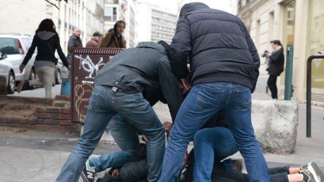 رجال شرطة في زي مدني يلقون القبض على رجل من بين المحتجين