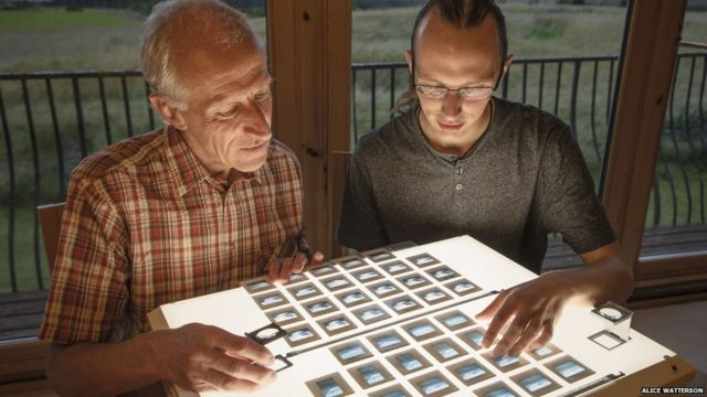 Colin e Kieran Baxter olham fotos que tiraram