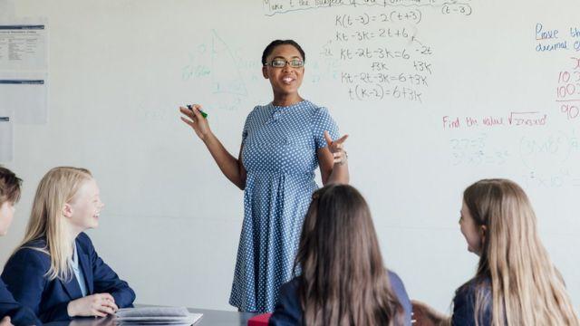 Professora ensinando fórmulas em uma classe