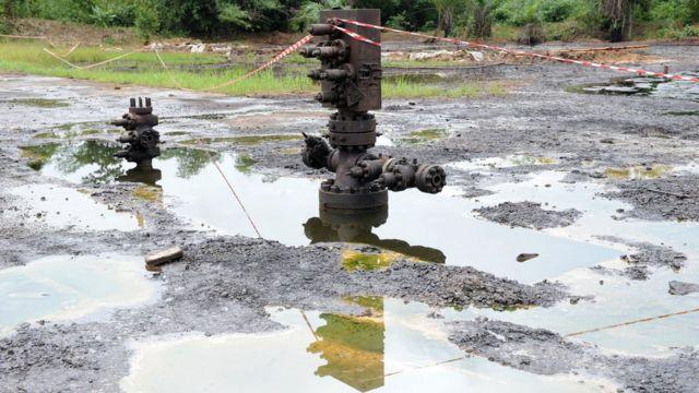 Terra poluída por derramamento de petróleo, com piscinas de óleo.