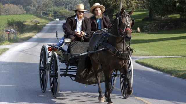 Dos amish se trasladan en una carreta.