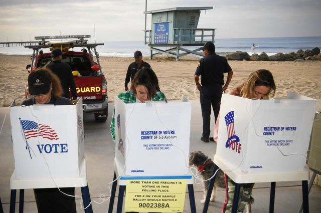 Young women vote in the mid-term elections at the Venice Beach Lifeguard station (as a surfer is seen riding in the background)