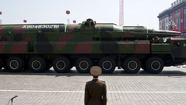 North Korean soldier stands guard in front of a military vehicle carrying what is believed to be a Taepodong-class missile Intermediary Range Ballistic Missile (IRBM), about 20 meters long, during a military parade to mark the 100 birth of the country's founder Kim Il-Sung in Pyongyang on 15 April 2012.