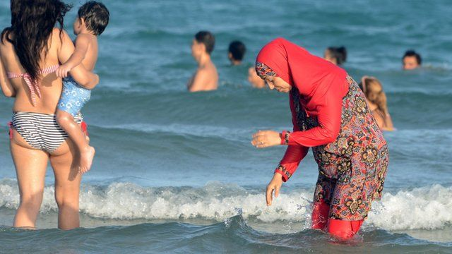 female swimmers in burkini (R) and a more 'traditional' swim suit (L)