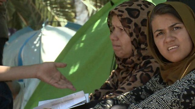 Close up of the hand of a charity worker gesturing towards two Afghan women refugees living in an Athens park