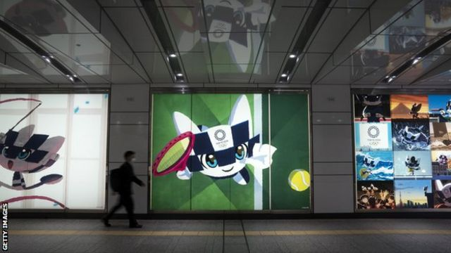 A commuter in a face mask walks in front of a poster of the 2020 Olympics mascot in Tokyo