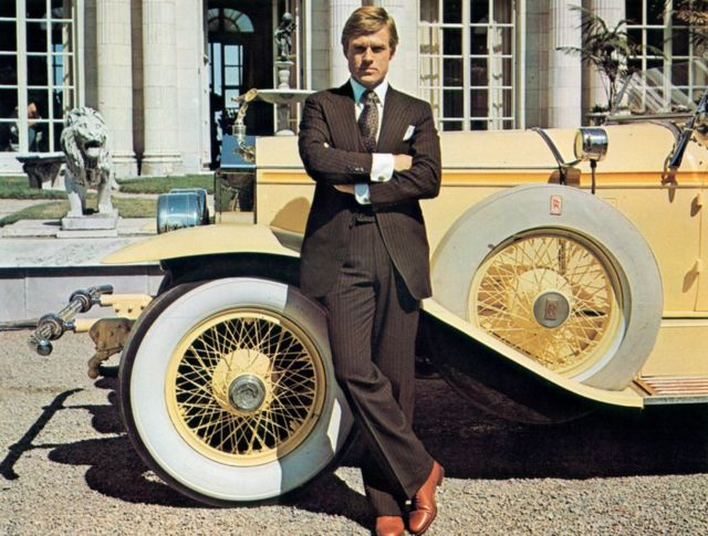"""Robert Redford leaning against luxurious car in a scene from the film """"The Great Gatsby"""", 1974."""