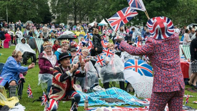 """Joseph Afrane, 52, in Union Jack clothing waves flags as members of the public in Green Park gather for a picnic and watch The Queen""""s Patronage on a big screen during """"The Patron's Lunch"""" celebrations"""