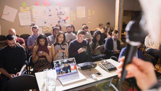 Una persona dado una charla frente a una audiencia en algo que parece un salón de clases