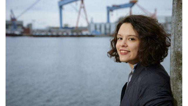 Foto de Delara Burkhardt sorrindo, de perfil, encostada de muro em frente a rio urbano