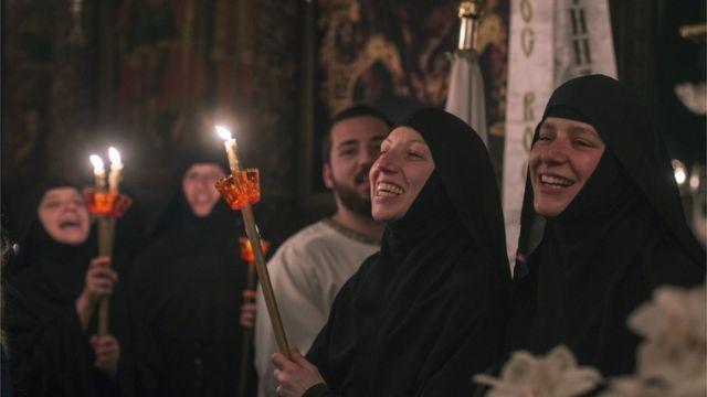 سيدات يضئن الشموع بكنيسة للمسيحيين الأرثوذكس في سكوبي بمقدونيا خلال احتفالات عيد الفصح