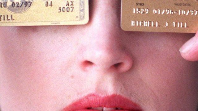 Una mujer sostiene dos tarjetas de crédito.