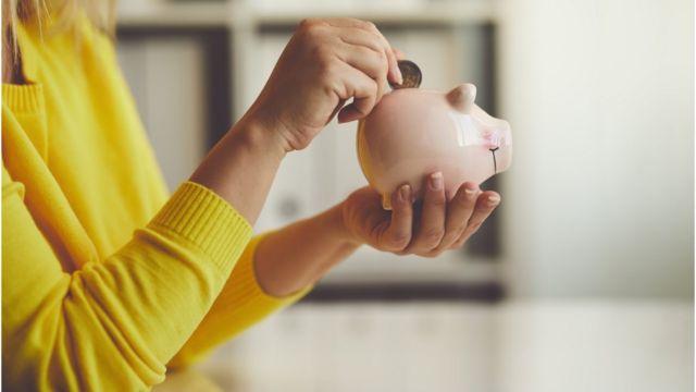 mulher guardando moeda em cofre