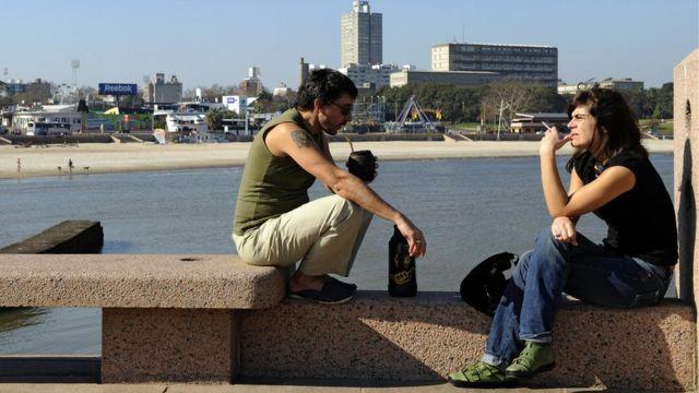 Hombre y mujer tomando mate en la rambla de Montevideo.