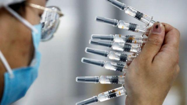 O funcionário de jaleco e máscara apareceu no perfil e continha várias doses do vidro da vacina.