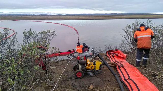 imagen muestra rescatistas mientras trabajan cerca de un gran derrame de diesel en el río Ambarnaya.