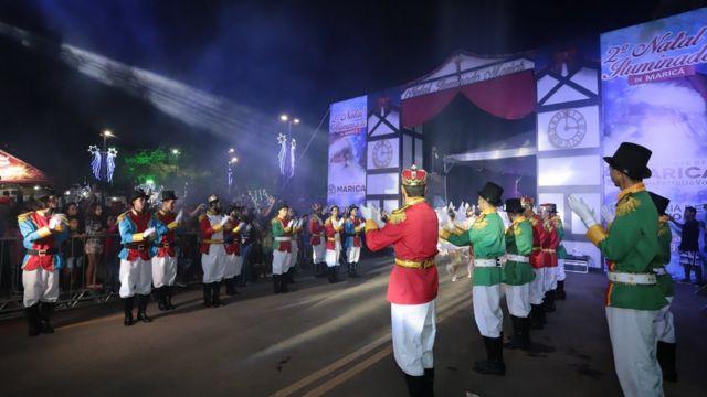 Dançarinos fantasiados participam de desfile noturno com tema de Natal