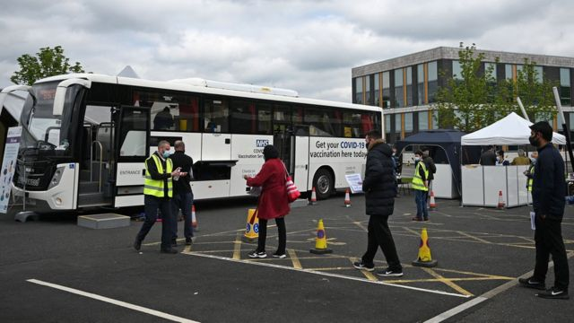 People queue for a vaccination at a bus in Bolton