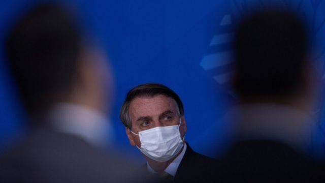 De máscara, Bolsonaro olha para o lado em evento