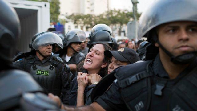 Manifestante é imobilizada durante protesto na passagem da tocha olímpica em Niteroi na terça-feira