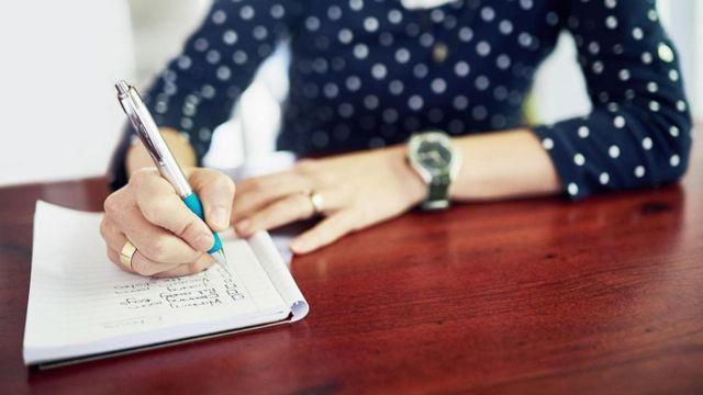 Mulher escreve uma lista