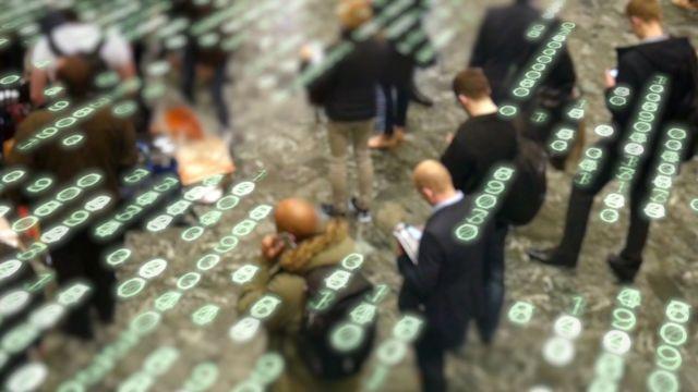 Pessoas caminham em calçada usando celulares, com sobreposição de dígitos na imagem representando códigos