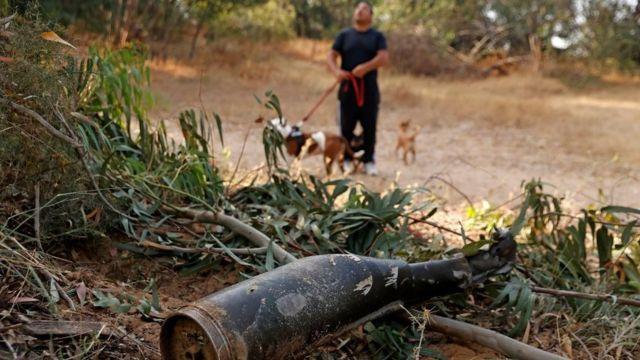 Un homme promène ses chiens à côté d'un missile détruit