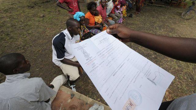 Un employeur de la société Sagem (R) vérifie un acte de naissance le 16 septembre 2008 à Ferkessedougou lors du deuxième jour de l'enregistrement électoral dans le pays.