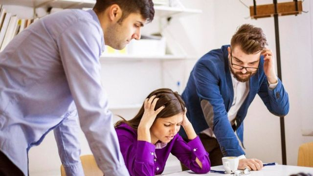 Tres personas sobre un escritorio, agobiadas por un problema laboral