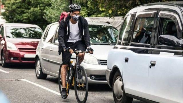 คนปั่นจักรยานและรถบนถนน
