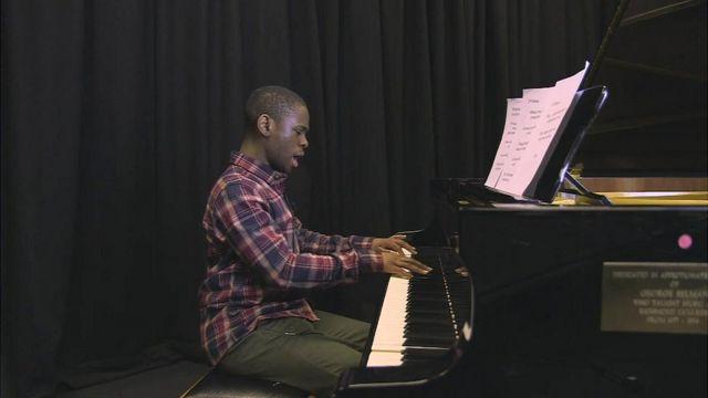 Michael interpretando al piano una pieza propia.