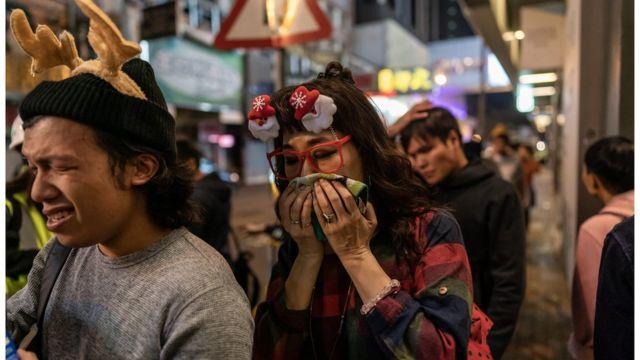 一些市民在警方發射催淚彈後掩臉離開。