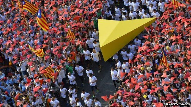 "Demonstrators hold a giant yellow cursor as they gather on Meridiana street and wave ""Estelada"" flags (pro-independence Catalan flags) during celebrations of Catalonia""s National Day"