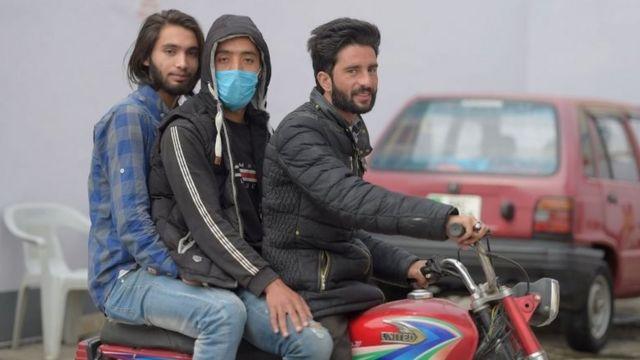 Homens em moto, um deles com máscara, no Paquistão