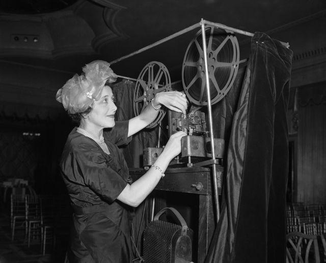 تصویر سیاه و سفید رز نیومن در حال کار با پروژکتور