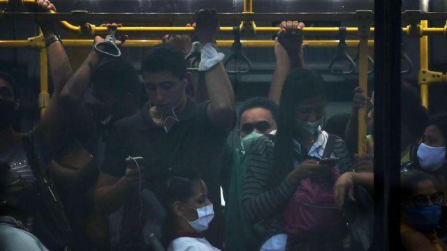 Ônibus lotado com pessoas com e sem máscara na pandemia