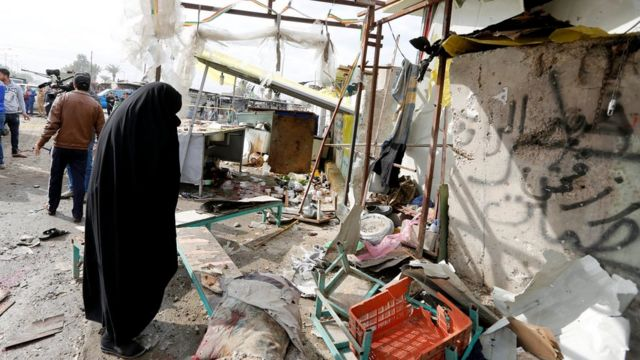 A woman looks at the scene of a suicide car bomb attack in Sadr City district of Baghdad (2 January 2017)